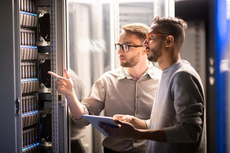 Two man wearing glasses looking at a server rack